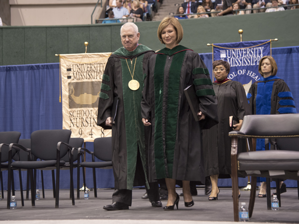 University of Mississippi Chancellor Dr. Dan Jones and Dr. LouAnn Woodward, UMMC vice chancellor for health affairs and dean of the School of Medicine, process to the stage during commencement.