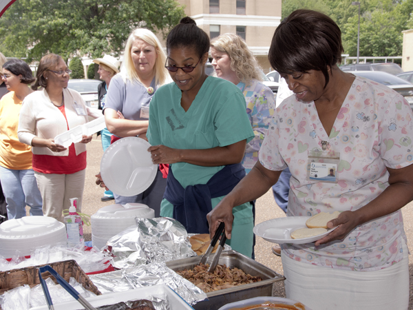 Celebrating UMMC Holmes County's 15th year in that community with a barbecue lunch are (far right) Donnie Washington, a licensed practical nurse; and Dr. Satira Perry, a physician in the hospital's family medicine clinic.