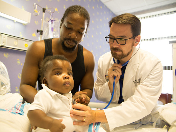 Boyte examines patient Queterrius Ellison, while his father Antonio holds him. Photo credit: The Schwartz Center for Compassionate Healthcare