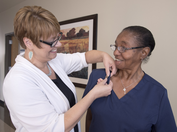 Frankie Gaines, a phlebotomist at UMMC's Adult Hematology lab at the Jackson Medical Mall, received her 50-year pin from Kim Meeker, administrator for Wiser Hospital perioperative and ancillary services.