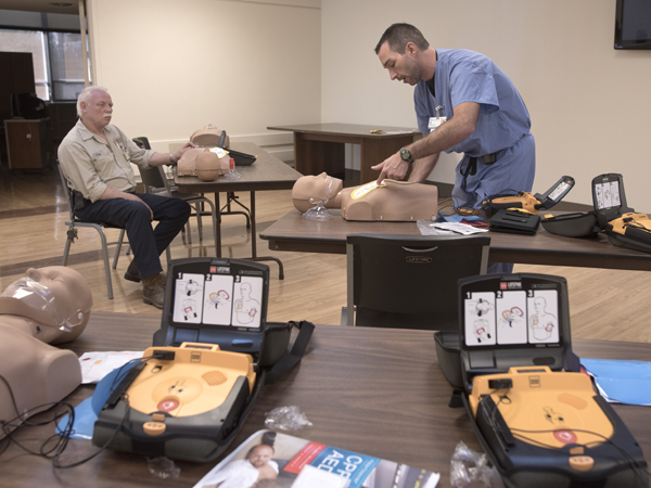 Jason Smith, right, emergency services manager, instructs a group of physical facilities employees, including Troy Bunn, how to use an AED.