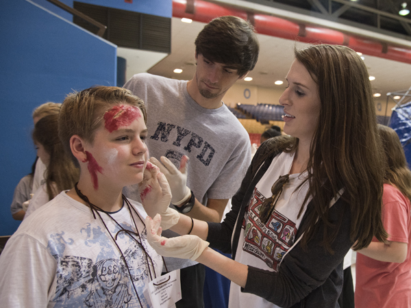 UMMC School of Nursing students Allen Lampton (center) and Maggie McDonald apply fake wounds and blood to the skin of Northwest Rankin Middle School eighth-grader Chris Russell