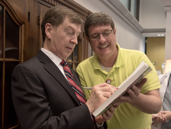 Dr. Robert Lewis, left, signs a copy of the Historical Atlas of Immunology for Dr. Stephen Stray, right,  associate professor of microbiology. The book was co-authored by Lewis and Dr. Julius Cruse, both of whom were honored by a retirement reception Thursday in the Rowland Medical Library.
