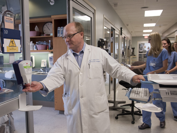 UMMC cardiothoracic surgeon Dr. Jay Shake takes time to foam his hands with sanitizer before entering a patient room on the cardiovascular intensive care unit.