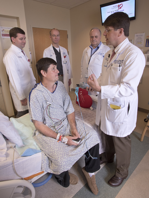 Dr. Matt deShazo (right) explains to heart transplant recipient Brad Fitzgerald how his heart monitoring device works as (top left) Dr. Craig Long, Dr. Charles Moore and Dr. Anthony Panos look on.