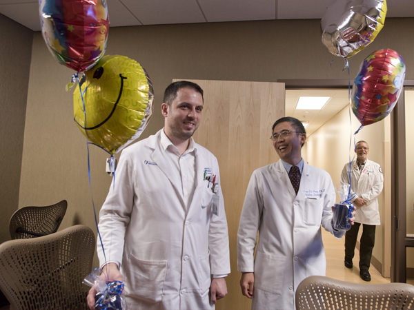 Markovich, left, and Yang were surprised with balloons and candy by coworkers and members of the AWARDS Team.