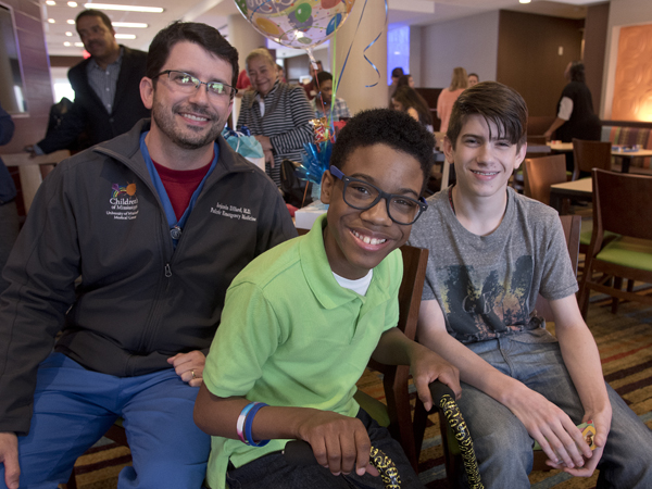 Morgan smiles with Dr. Benji Dillard, professor of pediatrics at UMMC, and his son Jacob.