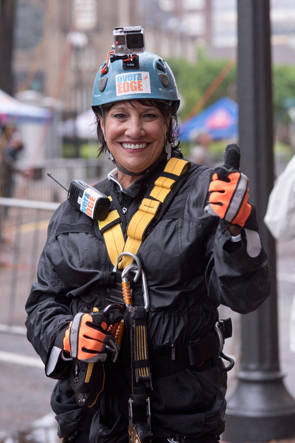 Friends of Children's Hospital board president Sara Ray gives a thumbs up to rappelling after coming down 14 stories in the Over The Edge with Friends fundraiser.