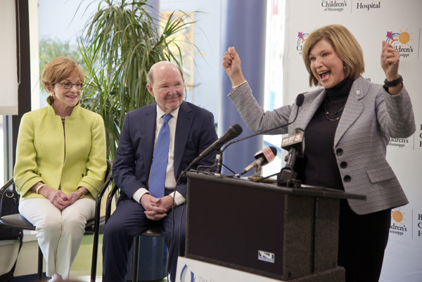 Woodward cheers at the announcement of a $10 million gift to Children's of Mississippi by Joe and Kathy Sanderson, looking on.