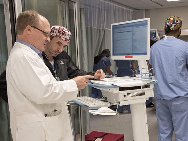 Dr. Jay Shake (left), associate professor of cardiothoracic surgery, and Dr. Sloan Youngblood, assistant professor of anesthesiology, review a patient's electronic medical record.