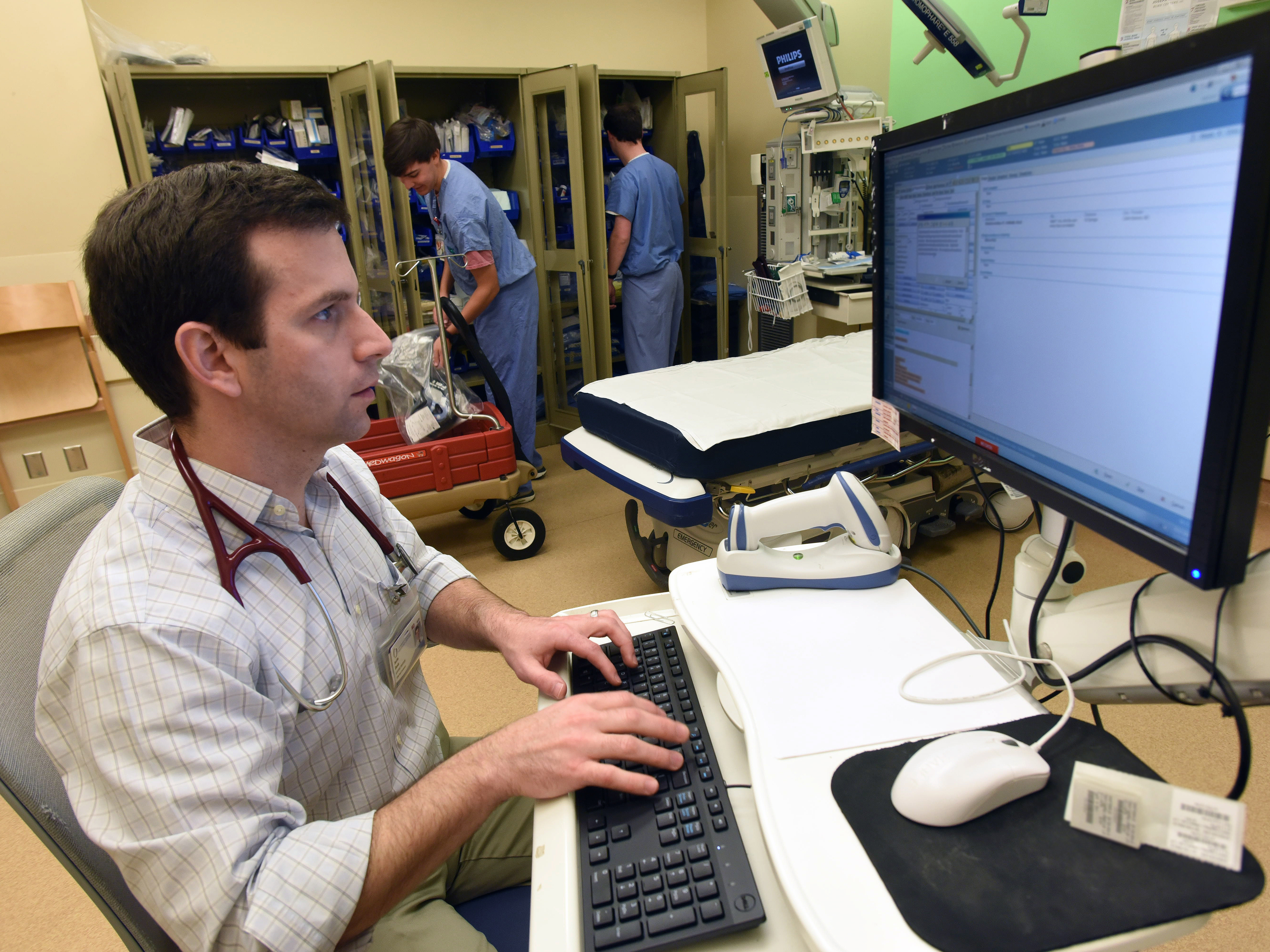 Dr. Justin Davis, assistant professor of pediatric emergency medicine, examines a patient's health records in the pediatric emergency department. A new information exchange with the Division of Medicaid allows him to also access those patient records.
