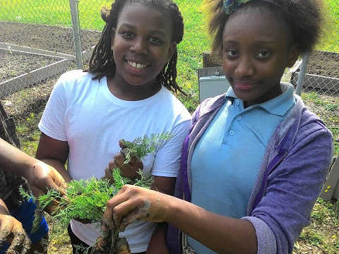 Shelby Middle School students proudly show off vegetables grown in their school garden.