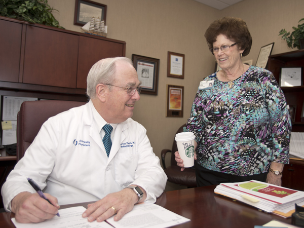 Fueled by two cups per day of Starbucks coffee, including one brought each morning by Bonita Herring, supervisor of business operations for the division, right, Thigpen has been called the most influential man in gynecologic oncology.
