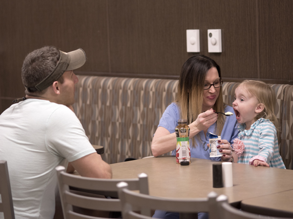 Allen (center) and 3-year-old daughter Maddie share a cup of yogurt in the UMMC cafeteria before Allen begins a night shift. Her husband and Maddie's father, Bear Allen, often brings Maddie to the hospital to visit when she works double shifts.
