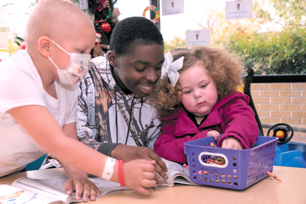Freddie Green Jr., center, spends time with Bentley Broussard, left, and his sister Brooklyn at the Children's Cancer Clinic.