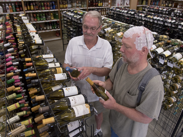 Newman, right, discusses wine with a customer, Bob Lundy of Wesson, at his family's store in Brookhaven. He wears the arrays and carries a battery powering them in a backpack during much of his working day.