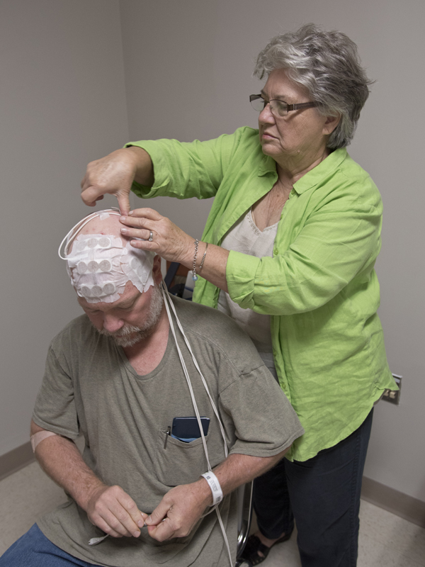 Newman's mother assists with placing the arrays after his recent checkup.