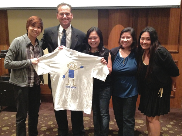 Giroux and a group of teachers in Singapore display a t-shirt that features the curriculum's mascot, Mat Man.