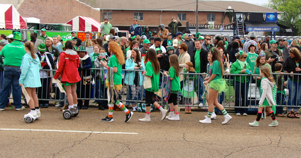 Volunteers sweep the parade route for donations.
