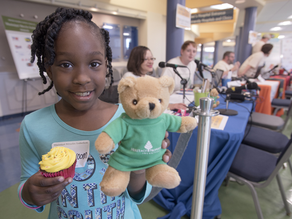 "Malia Croom receives a cupcake and a new friend, a Heritage Properties ""Blair Bear"" during her Radiothon appearance."