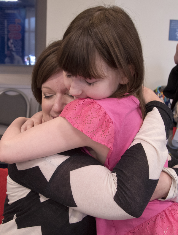 Caylen Ayscue hugs Evelyn Johnson, an on-air personality for River 101.3, during the Mississippi Miracles Radiothon.