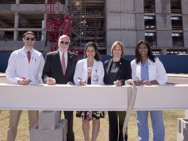 Among those who signed the construction beam during Monday's topping-out ceremony are, from left, second-year medical student John Lippincott; former UMMC vice chancellor Dr. James Keeton, distinguished professor and advisor to the vice chancellor; fourth-year medical student Sara Ali; Dr. LouAnn Woodward, vice chancellor for health affairs and dean of the School of Medicine; and first-year medical student Michelle Wheeler.