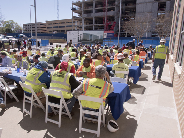 Members of the construction crew for Roy Anderson Corp. Contractors are treated to lunch during Monday's topping-out ceremony for the new School of Medicine building.