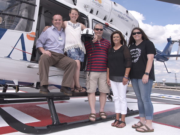 Abby is pictured with the critical care paramedic on her flight, Sam Marshall (left) and her family members: dad Ken, mom Melinda and sister Bailey.