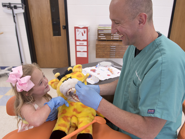 Seeing a Smile Train advertisement in a magazine while attending therapy with his daughter, Leighton, left, led Myrick to consider a career in dentistry.