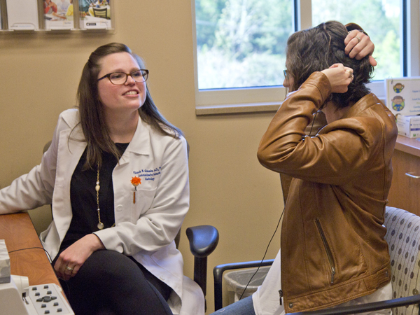 Dr. Vicki Gonzalez, left, observes as Edmonson demonstrates positioning her cochlear implant.