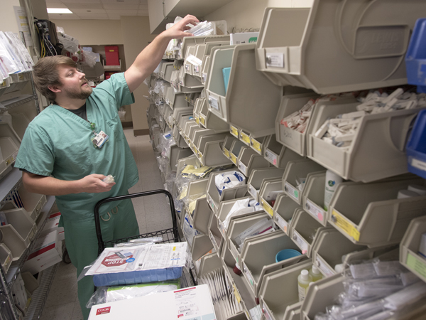 Matt Harris,, a registered nurse in the Medical ICU, stocks bins with supplies needed for critical care.