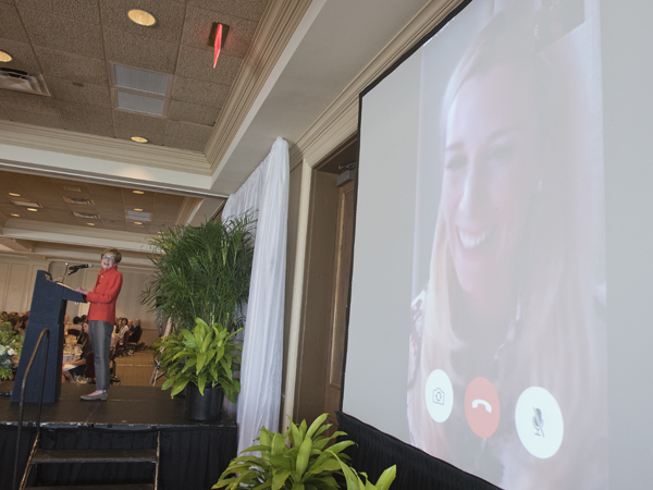 Children's of Mississippi capital campaign chair Kathy Sanderson, at the podium, chats with honorary campaign chair Abby Manning via FaceTime.