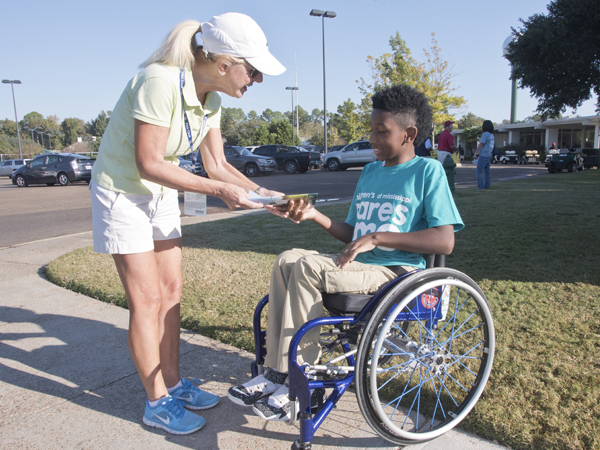 Diane Gribble of Dallas, mom of Sanderson Farms Championship winner Cody Gribble, meets another athlete: K.J. Fields of Mount Olive. K.J., though using a wheelchair, plays basketball, participates in track and field events and has even gone surfing. He was among greeters for Children's of Mississippi.
