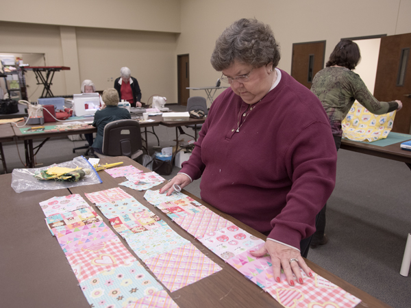 Roanoke McDonald puts quilt squares in place during a meeting of the Susannah Stitchers.