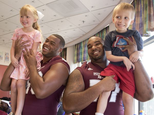 Campbell and his sister Avery are entertained by Mississippi State University football players Ryan Brown, left, and Rufus Warren during a team visit July 2015 to Batson Children's Hospital.