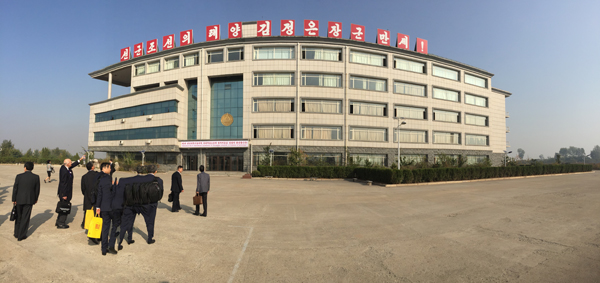 Attendees of the 3rd International Conference of Science and Technology approach the main academic building at Pyongyang University of Science and Technology.