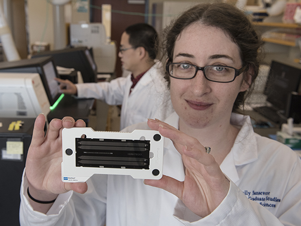 Emily Sansevere, a fifth-year graduate student, displays a genome sequencing chip. By loading millions of DNA fragments on a chip, she can then determine the entire genetic sequence, or genome, of a bacteria such as Staphylococcus aureus.