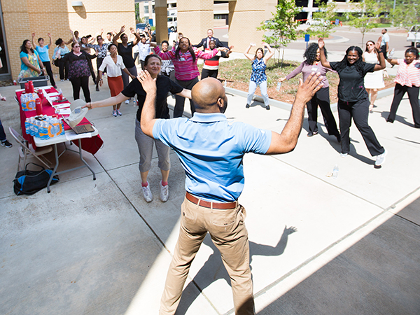 Ronald Woods, University Wellness medical integration coordinator, center, leads participants in warm-up exercises before taking a lap around the UMMC campus.