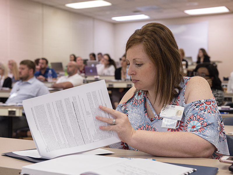 April Loftin, an enrollee in the School of Nursing's RN-BSN bridge program, dives into the paperwork during orientation.