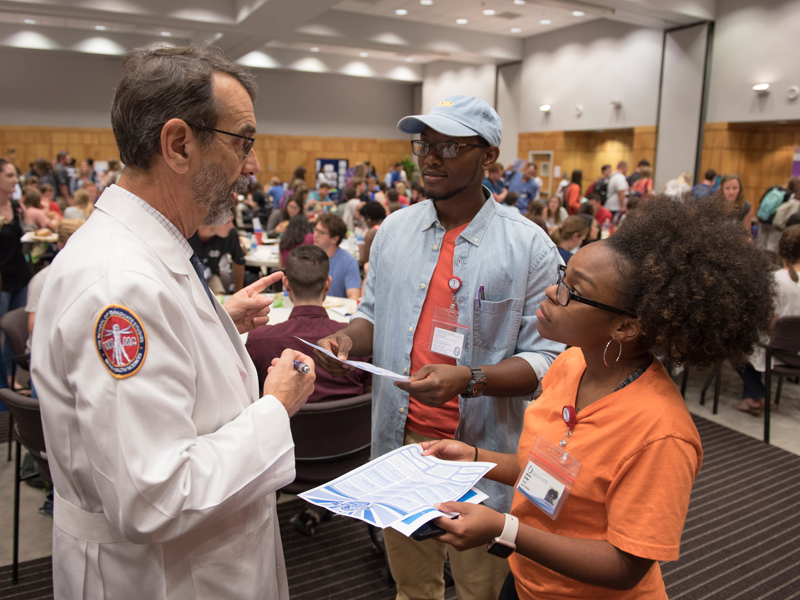 Dr. Rob Rockhold, left, talks with first-year medical students Lorenzo Spencer and Anissa Butler.
