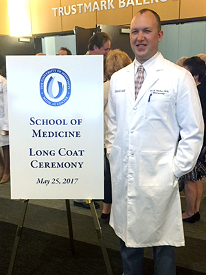 Harber poses for a picture after receiving his long white medical coat.