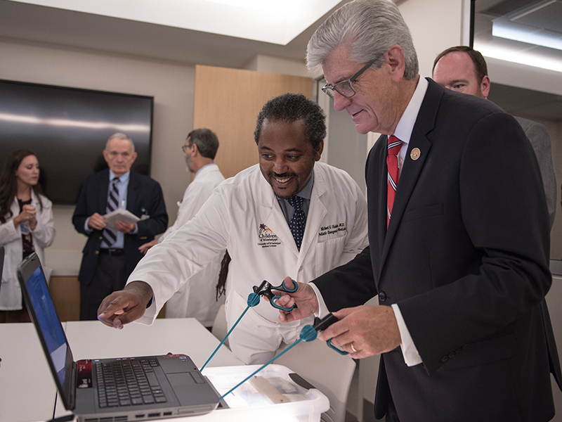 Dr. Michael Holder, left, associate professor of pediatric emergency medicine and executive director of simulation and interprofessional education, shows Gov. Phil Bryant how to play a game that simulates performance of surgery.