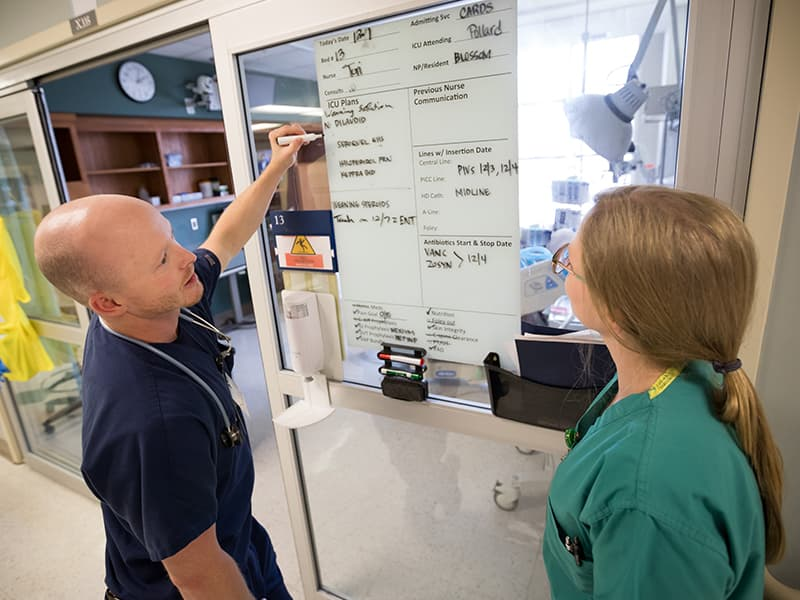 Dale Brewer, left, R.N., and Laura Stevens, R.N., review patient information on a communication board in the Cardiac Intensive Care Unit. The Joint Commission gave the adult critical care units kudos for their use of the boards.