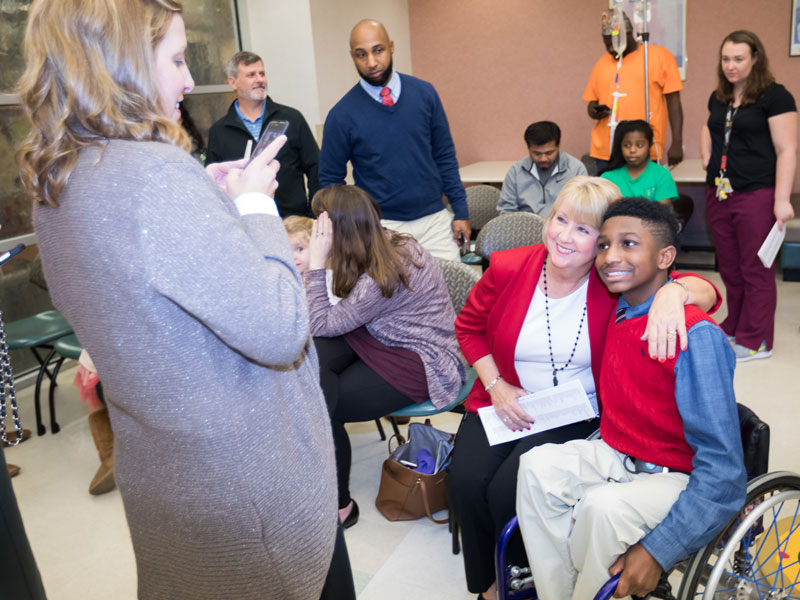 Kelly Scrivner snaps a photo of Mississippi First Lady Deborah Bryant and Batson Children's Hospital patient K.J. Fields, who lit the hospital Christmas tree during BankPlus Presents Light A Light. The event, the oldest of Friends of Children's Hospital fundraisers, is the traditional start of the holiday season at UMMC.