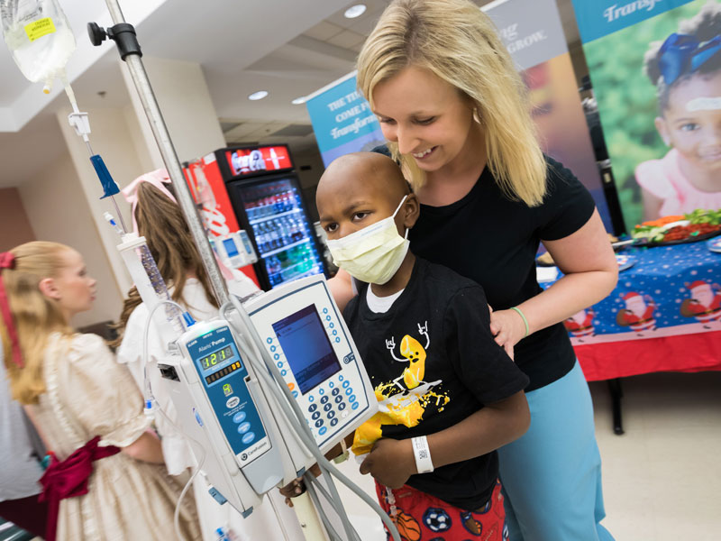 Child life specialist Tiffany Key and patient Rico Jones Jr. of Canton enjoy the reception following BankPlus Presents Light A Light. The event was moved to the Wiser Hospital for Women and Infants cafeteria due to the start of construction for a new children's tower adjacent to Batson Children's Hospital.
