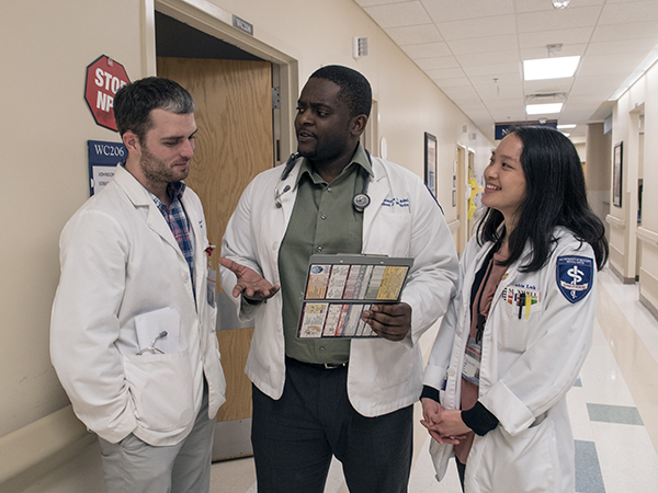 During his internal medicine rotation, Omonuwa Adah, center, sounds out fellow medical students Eric Wilkerson and Adria Luk.