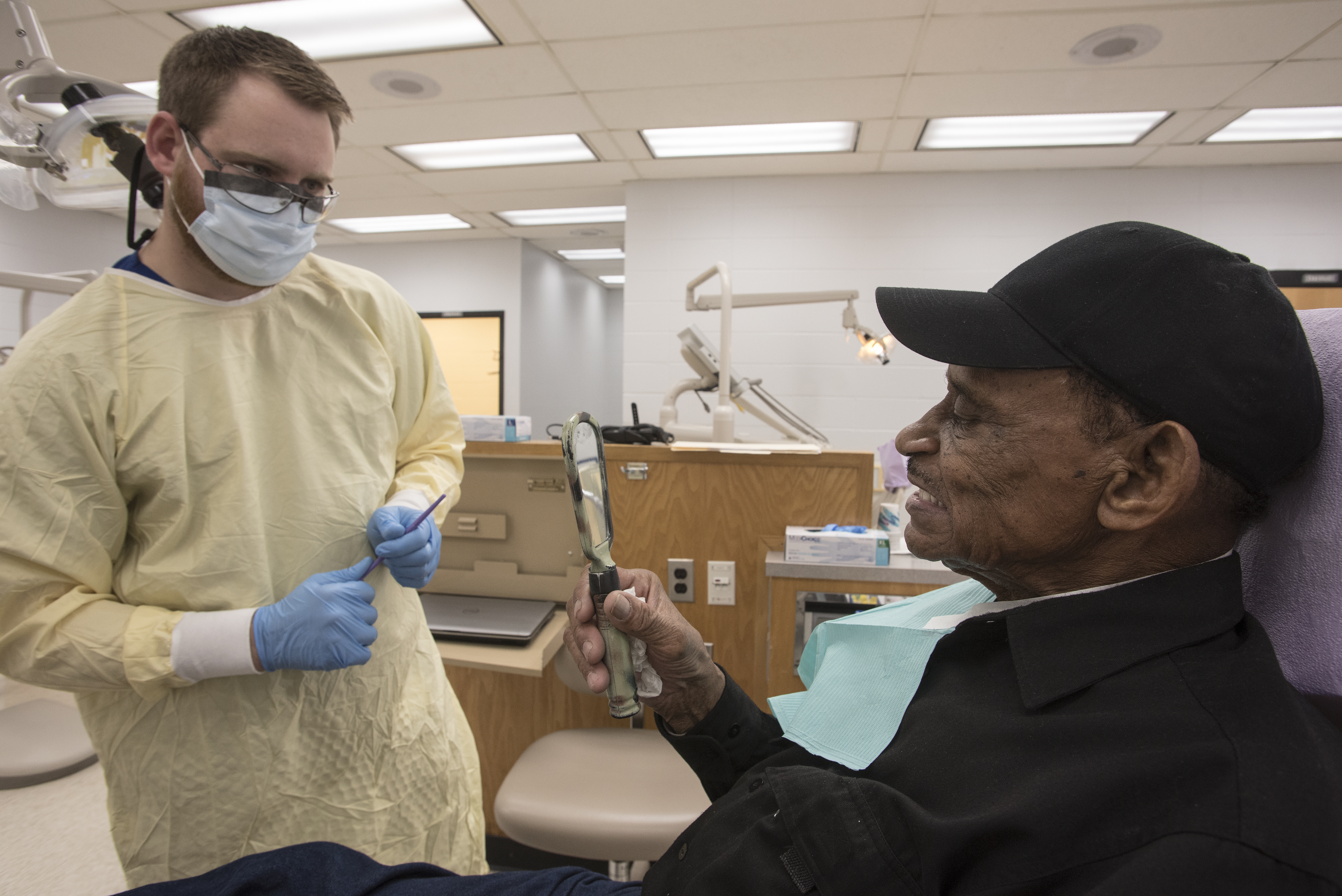 Glover, left, makes minor adjustments to Sutton's dentures during a fitting appointment on Wednesday.