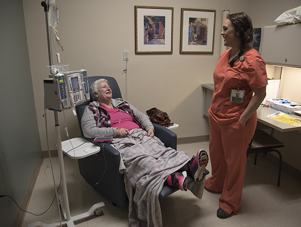 Cancer Institute registered nurse Heather Zamora cares for Hinton during her final chemo infusion.