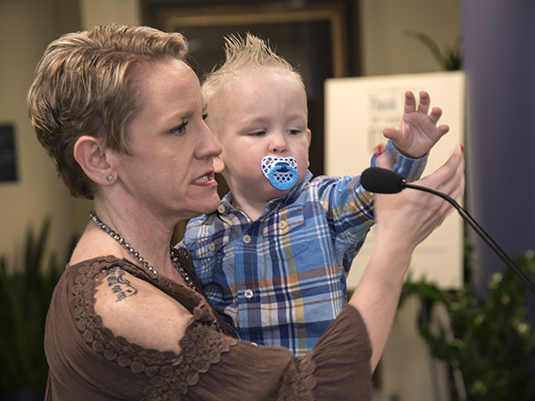 Two-year-old Jack Reynolds reaches for the microphone as mom Morgan Strickland tells of the importance of neonatal transport to her family.