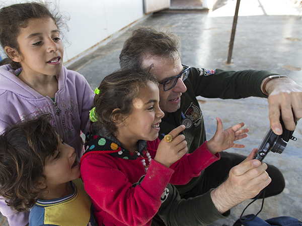 Bakdash shows children at the Al Zaatari refugee camp a camera.